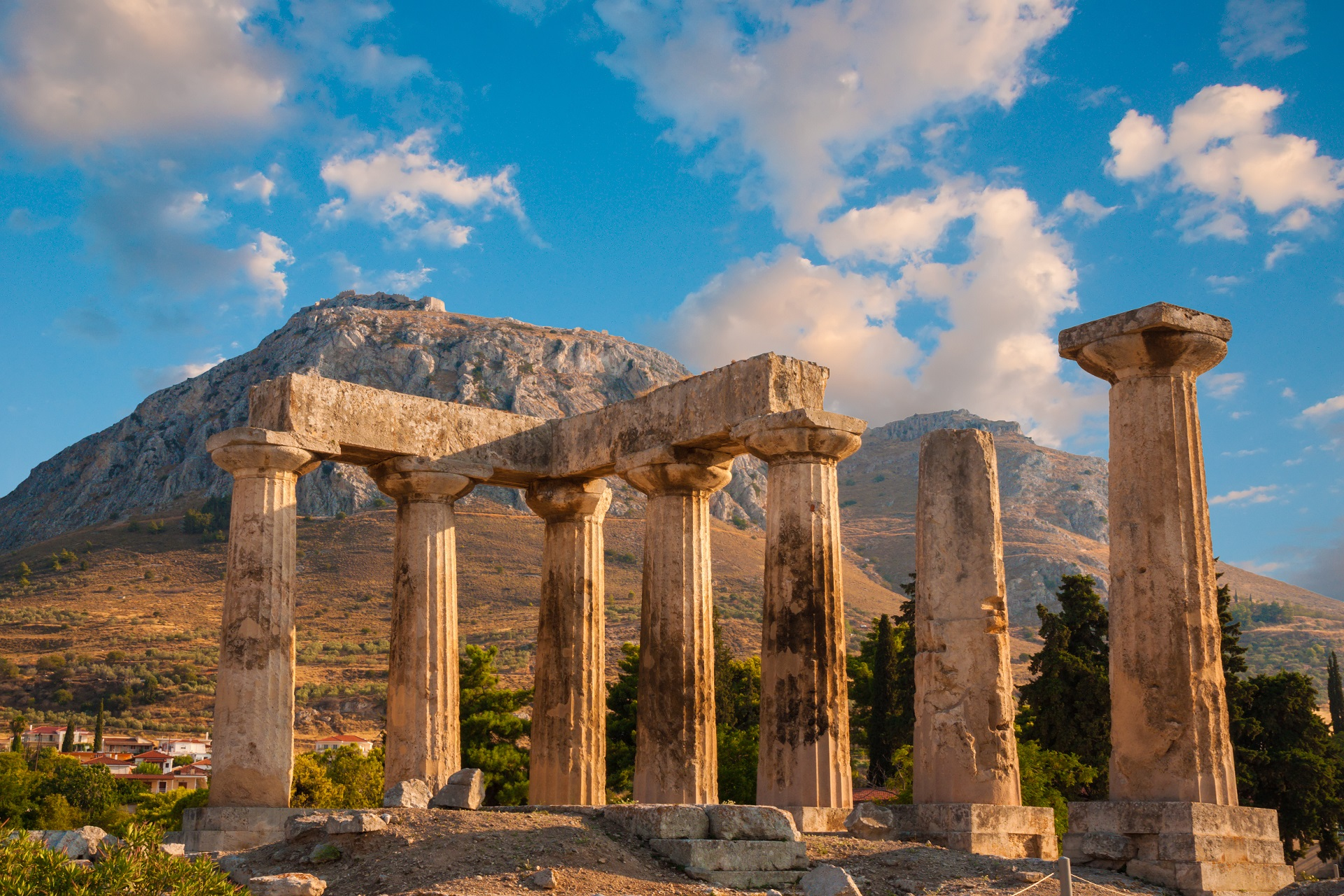 Ruins of Appollo temple with fortress at back in ancient Corinth, Greece