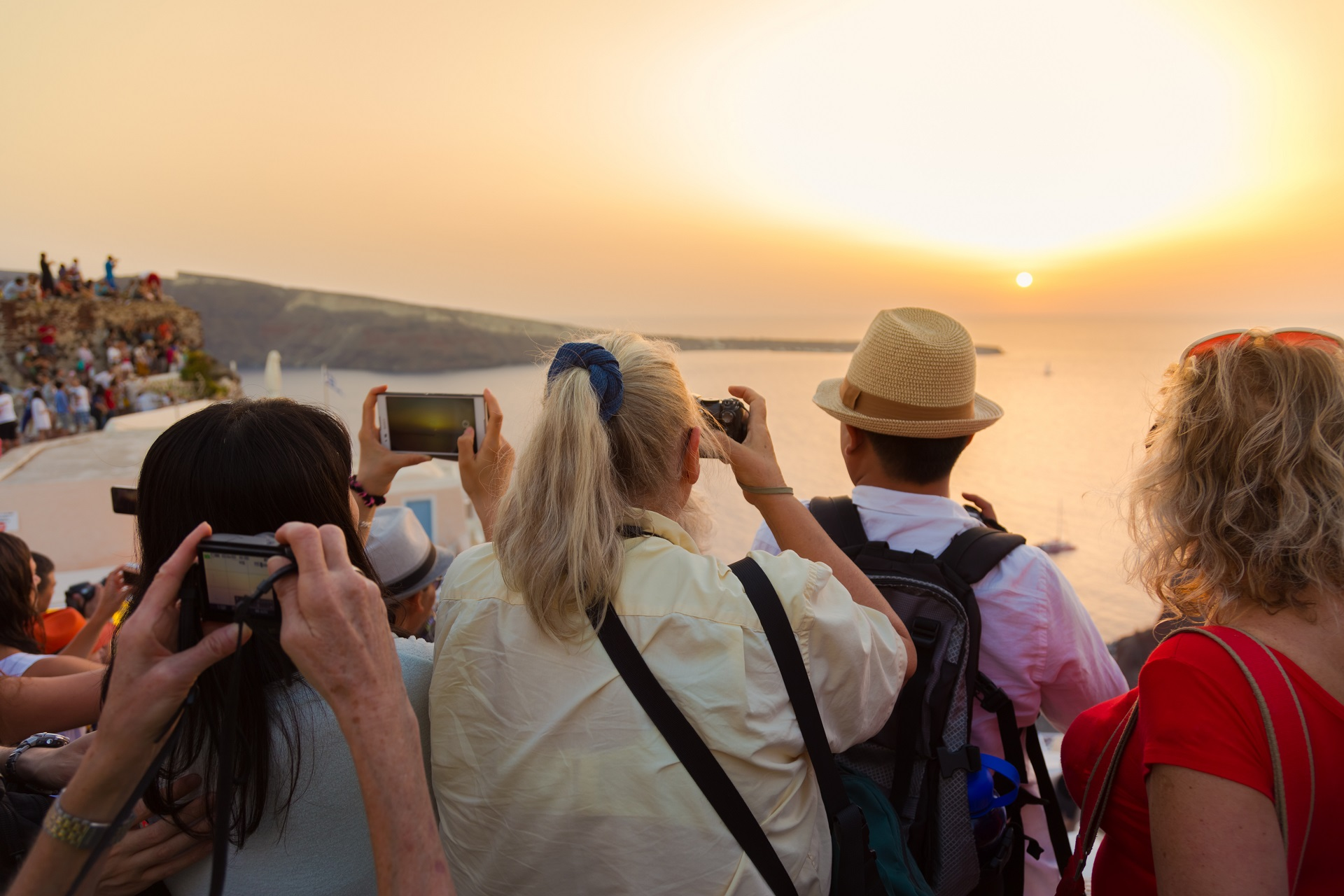Large group of tourist watching and taking photos of famous sunset view in Oia village on Santorini island in Greece